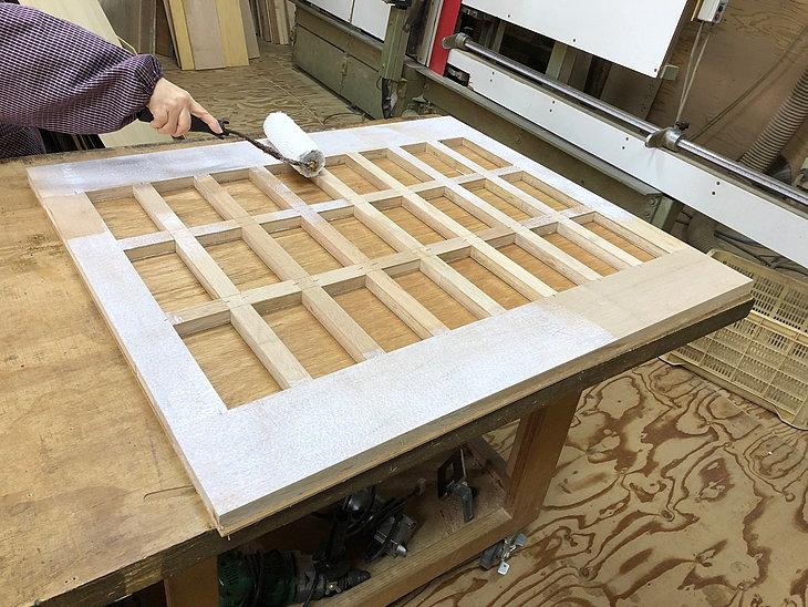 メラミン化粧板貼り仕上下のフラッシュパネル内部構造に接着剤を塗布