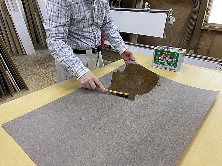 メラミン化粧板の裏面と貼る面の両方に速乾接着剤を素早く均一に塗りのばします。